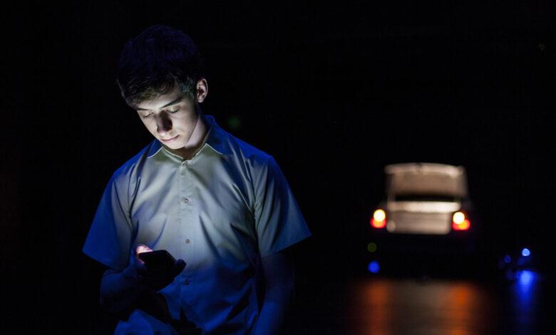 miúdo olha a tela do telemóvel no escuro